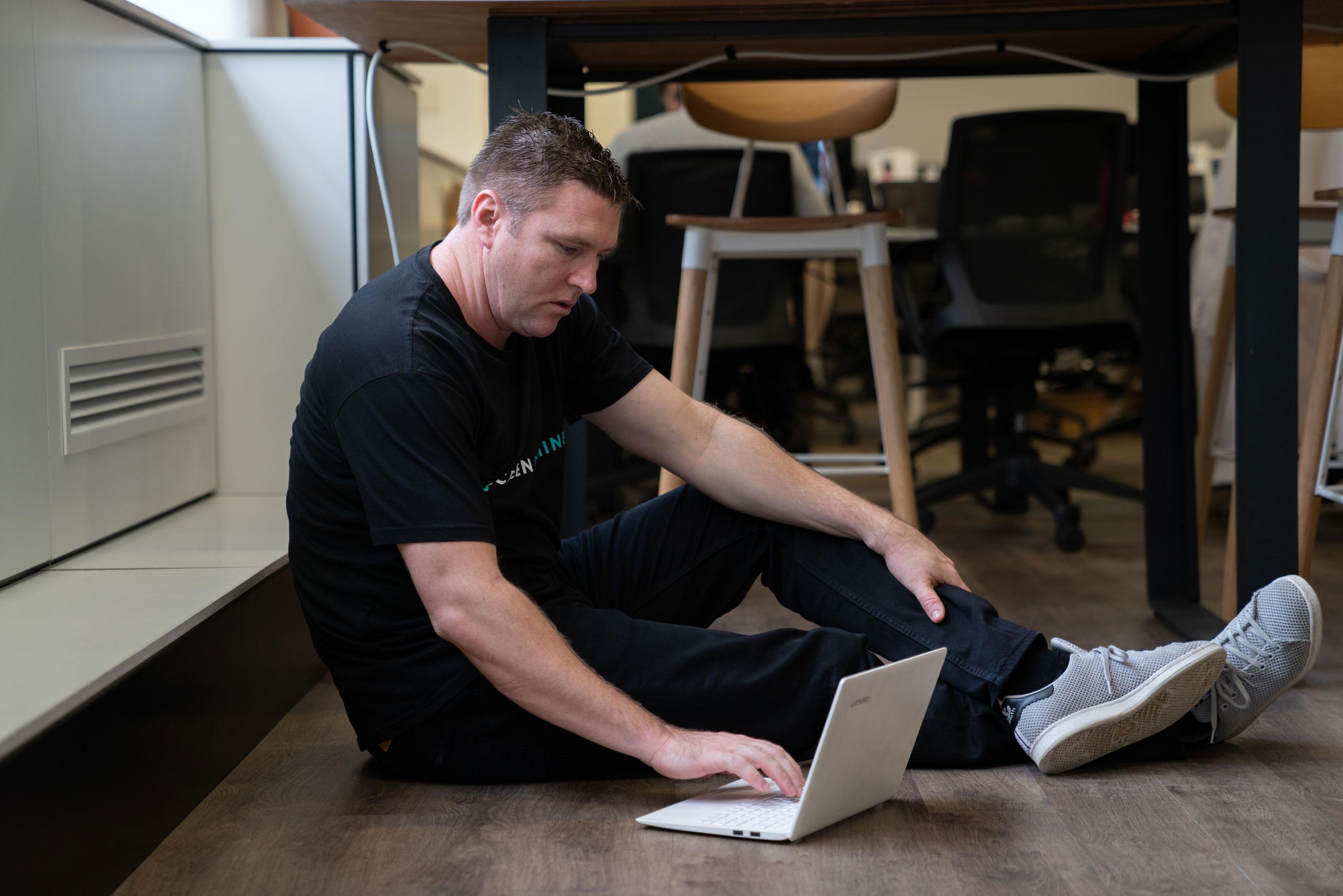 Start up founder Morgan of Screen Dopamine working on laptop under desk