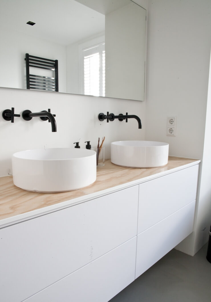 twin black faucets in white bathroom