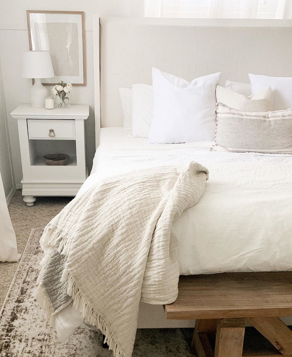 White bedroom linen sheets and timber bench