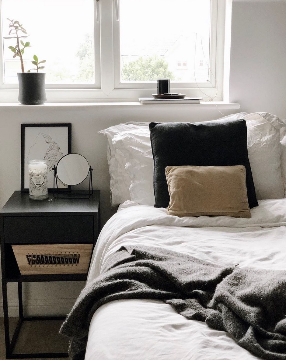 White bedroom with black side table and decor