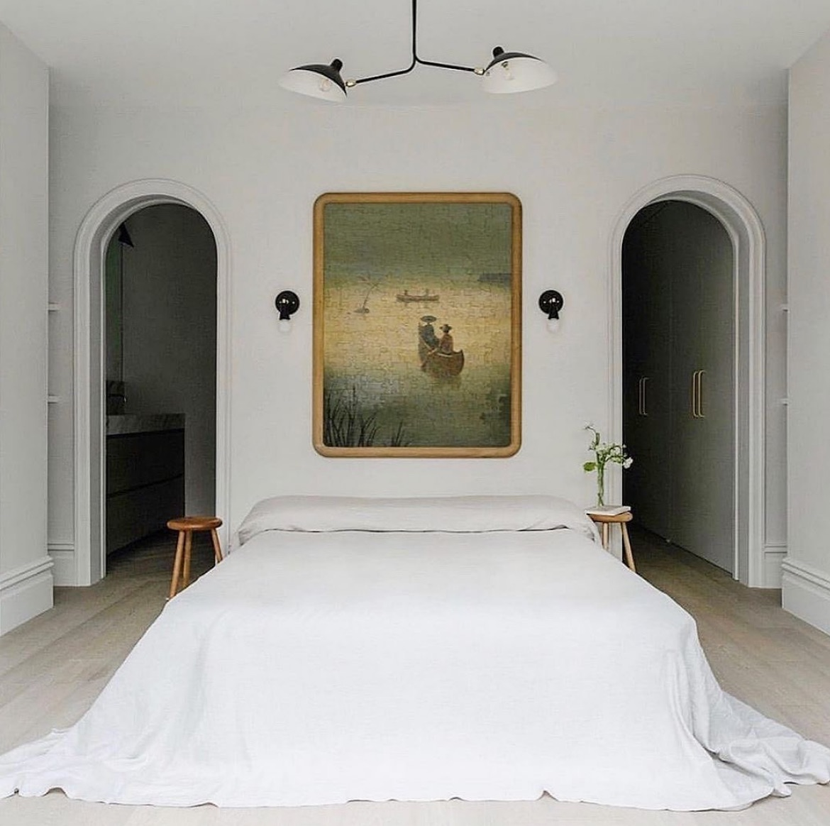 Master white bedroom with large artwork above bed