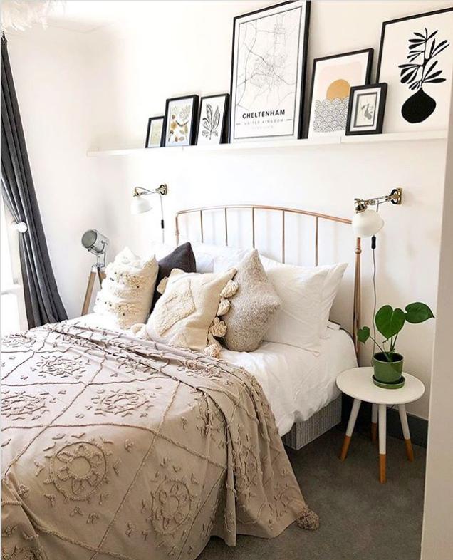 Picture frames on floating shelf above bed in a Scandinavian bedroom