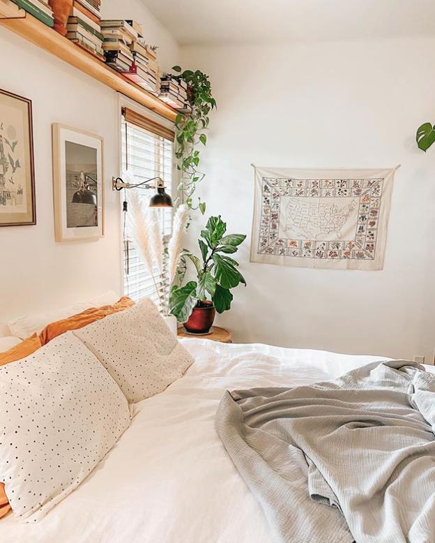 Bookshelf above bed in Scandinavian bedroom