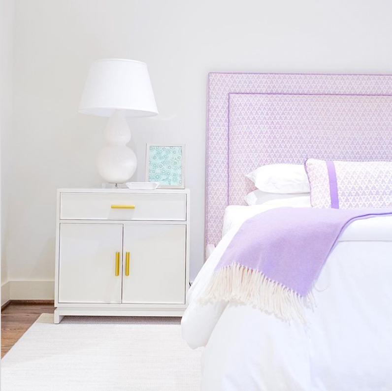 Pastel bed frame in a white bedroom