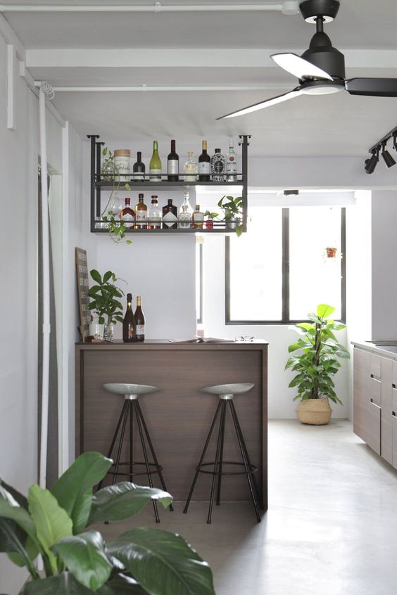 home bar with stools and overhead shelving