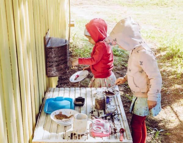 girls playing in their outdoor mud kitchen