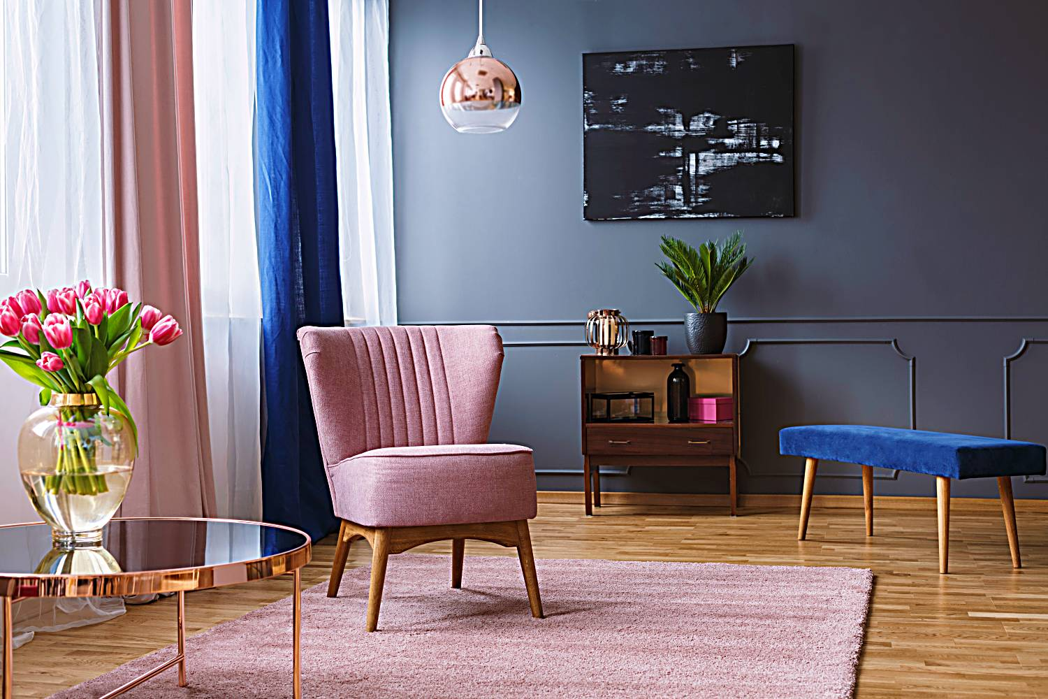 pink armchair standing on a rug and under a lamp in spacious living room interior, next to a table with flowers and in front of a shelf next to a grey wall with dark painting