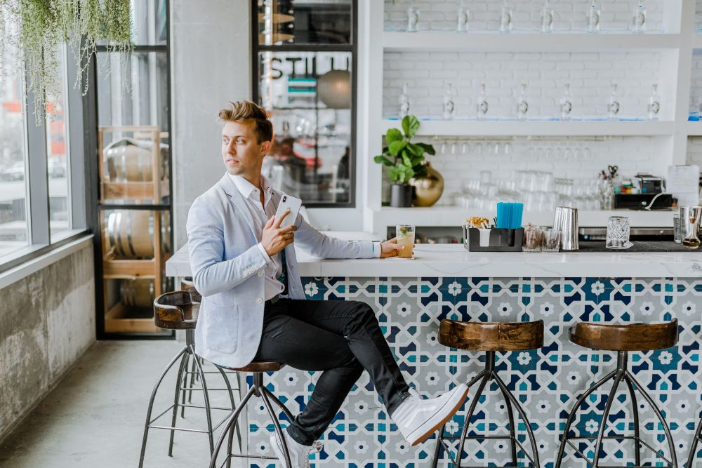 blond man sitting on bar stool at home with drink in hand