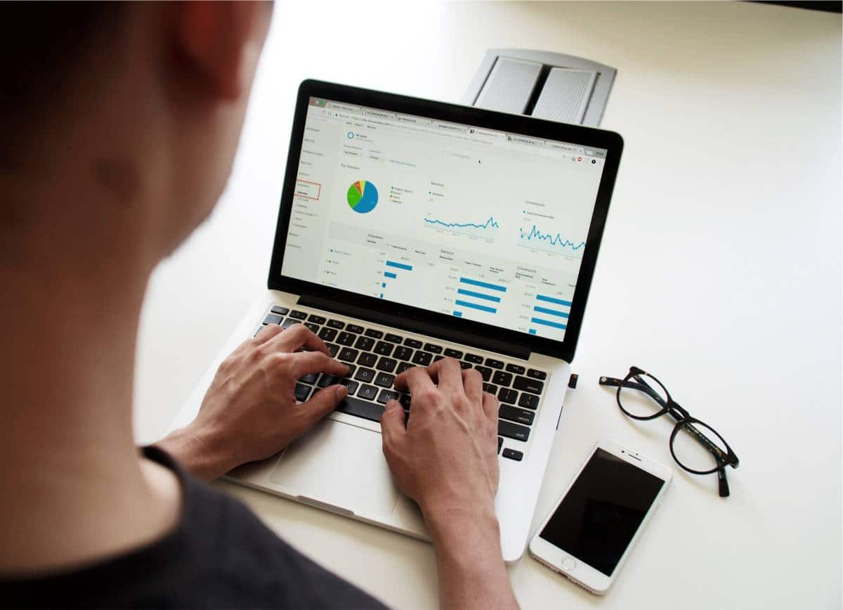man looking at online charts on laptop