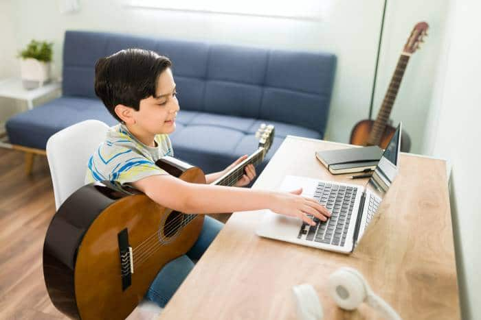 boy learning how to play the guitar online