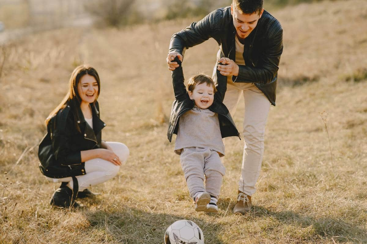family playing soccer outdoors